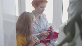 Cute little daughter examines sewing accessories and learning how to sew while her red-haired mother sews clothes