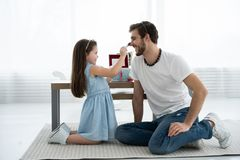 Cute little daughter and her handsome young dad in crowns are playing together in child`s room. Girl is doing her dad a. Makeup stock images