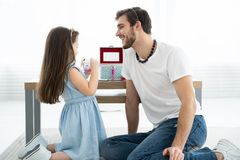 Cute little daughter and her handsome young dad in crowns are playing together in child`s room. Girl is doing her dad a. Makeup stock photos
