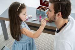 Cute little daughter and her handsome young dad in crowns are playing together in child`s room. Girl is doing her dad a. Makeup stock image
