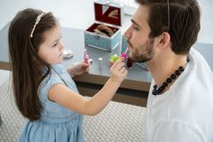 Cute little daughter and her handsome young dad in crowns are playing together in child`s room. Girl is doing her dad a. Makeup royalty free stock image