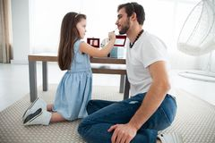 Cute little daughter and her handsome young dad in crowns are playing together in child`s room. Girl is doing her dad a. Makeup royalty free stock images