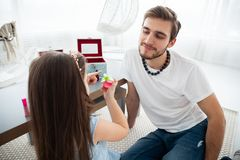 Cute little daughter and her handsome young dad in crowns are playing together in child`s room. Girl is doing her dad a. Makeup stock photo