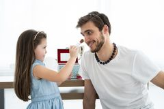 Cute little daughter and her handsome young dad in crowns are playing together in child`s room. Girl is doing her dad a. Makeup royalty free stock photo