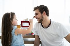 Cute little daughter and her handsome young dad in crowns are playing together in child`s room. Girl is doing her dad a. Makeup royalty free stock photography