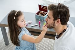 Cute little daughter and her handsome young dad in crowns are playing together in child`s room. Girl is doing her dad a. Makeup stock photography