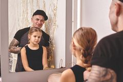 Cute little daughter and her tattoed dad are playing together near a mirror. Dad is doing his daughter`s hair. Family royalty free stock photography