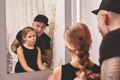 Cute little daughter and her tattoed dad are playing together near a mirror. Dad is doing his daughter`s hair. Family royalty free stock photo