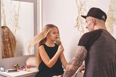 Cute little daughter and her tattoed dad are playing together near a mirror. Dad is doing his daughter`s hair. Family stock images