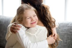 Cute little daughter hugging mother, kids love for mom concept. Cute little daughter hugging mother holding tight, mum and happy preschool or school girl Royalty Free Stock Image