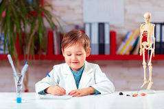 Cute little doctor writing notes in lab Royalty Free Stock Image