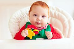 Cute little elf, infant baby sitting in highchair Stock Photo