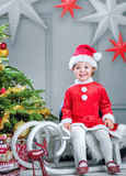 Cute little elf sitting on the sledge. Cute little elf sitting on the Christmas sledge Stock Photo
