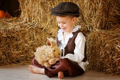 Cute little european boy in the cap with blue eyes. And bunny Royalty Free Stock Photography