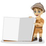 Cute little explorer boy in a safari outfit showing giant book open Royalty Free Stock Photos