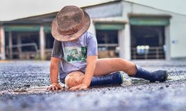 Cute little farmboy sitting in a puddle royalty free stock photo