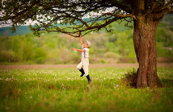 Cute little farmer boy playing under an old tree Stock Images
