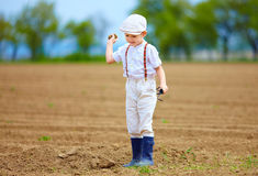 Cute little farmer on spring field, with earth clod in hand Stock Photography