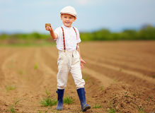 Cute little farmer on spring field  holding earth clod Royalty Free Stock Images