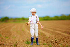 Cute little farmer on spring field  holding earth clod Royalty Free Stock Photography