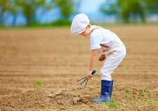 Cute little farmer working with spud on spring field Royalty Free Stock Photos