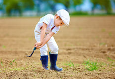 Cute little farmer working with spud on spring field Stock Photos