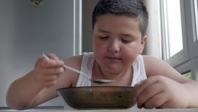 Cute little fat boy dining in kitchen, eating a tablespoon of soup, concept childhood obesity and gluttony. Cute little fat boy dining in the kitchen, eating a stock video footage
