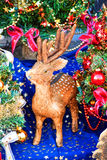 Cute little fawn next to Christmas trees. Cute little fawn next to decorated with ribbons and colorful toys little Christmas trees Stock Image