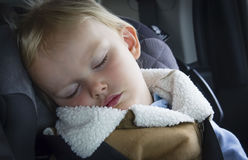 Cute little female caucasian toddler sleeping in car seat. Stock Images