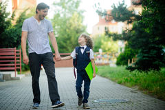 Cute little first grader is going with his father to school. Royalty Free Stock Photography