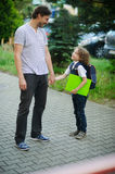 Cute little first grader is with his father in the school yard. Stock Image
