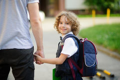 Cute little first grader student going to school with dad. He clings to the hand of the father. The boy turned around and smiled. Behind the schoolboy's Stock Photos