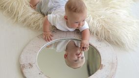 A little five-month newborn baby is playing with a mirror at home lying on bed. stock video footage