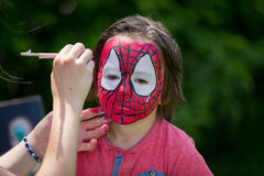 Cute little five years old boy, having his face painted as spid Stock Photo
