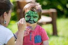 Cute little five years old boy,. having his face painted on his Stock Photos