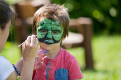 Cute little five years old boy,. having his face painted on his Stock Photography