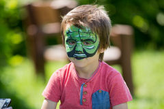 Cute little five years old boy,. having his face painted on his Stock Image