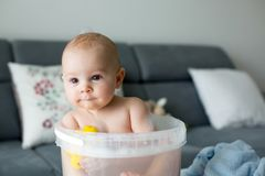 Cute little four month old baby boy, playing in bucket full with royalty free stock photos