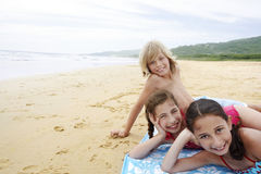 Cute Little Friends Reclining On Sandy Beach Stock Photo