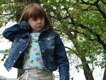 Cute Little Frown. Little girl standing outside in jean jacket frowning Stock Photography