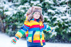 Cute little funny boy in colorful winter clothes having fun with Stock Photo