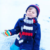 Cute little funny boy in colorful winter clothes having fun with Stock Image