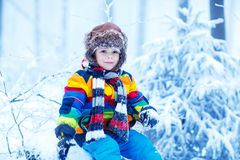 Cute little funny boy in colorful winter clothes having fun with Stock Images