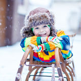 Cute little funny boy in colorful winter clothes having fun with Stock Photos