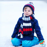 Cute little funny boy in colorful winter clothes having fun with Royalty Free Stock Image