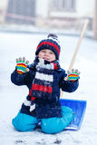 Cute little funny boy in colorful winter clothes having fun with Royalty Free Stock Photos