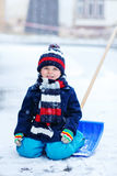 Cute little funny boy in colorful winter clothes having fun with Stock Photography