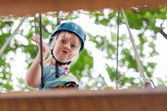Cute little funny caucasion blond girl in helmet having fun walking by rope suspension bridge in adventure park. Children outdoor extreme sport activities stock photo