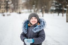 Cute little funny child in colorful winter clothes having fun with snow, outdoors during snowfall. Active outdoors leisure with ch stock photo