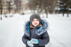 Cute little funny child in colorful winter clothes having fun with snow, outdoors during snowfall. Active outdoors leisure with ch royalty free stock image